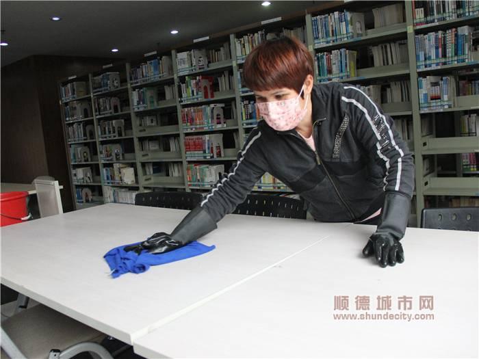 北滘圖書館工作人員對桌子進行消毒處理.jpg