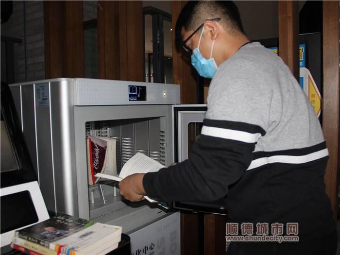 北滘圖書館工作人員將圖書放入自助圖書殺菌機進行消毒.jpg